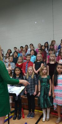 Mrs. Cooper conducting children's choir for Christmas Concert