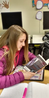 Middle Schooler enjoying a book during Stop, Drop, & Read Day!
